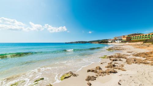 Primo piano bagnasciuga Le Bombarde, mare turchese, sabbia fine e qualche roccia affiorante