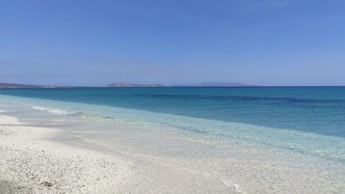 Focus sulla riva di Ezzi Mannu, sabbia fine grigia mista a piccoli ciottoli di quarzo, mare turchese